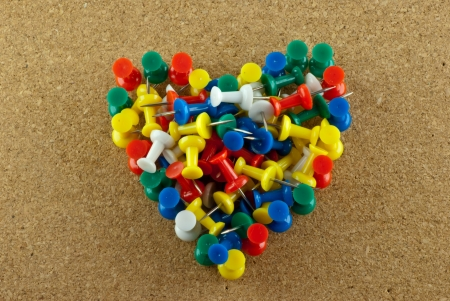Colorful pins pile on corkboard in heart shape