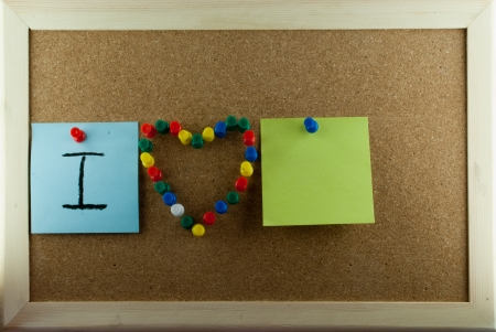 confine: Post-it note and heart shape pins on corkboard