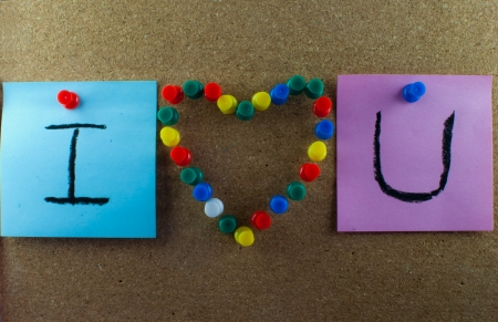 confine: Post-it note and heart shape pins on corkboard - close up