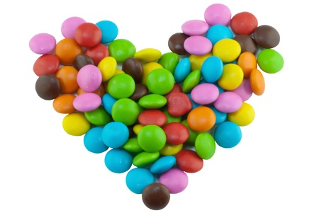 Colorful candies lay in heart shape on white background photo