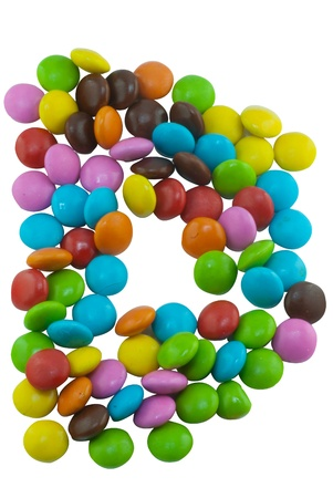 Colorful candies lay in letter U in front of white background photo