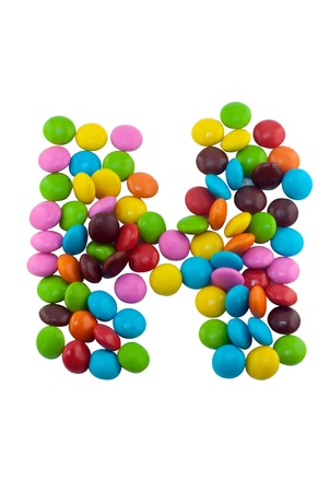 Colorful candies lay in letter H in front of white background photo