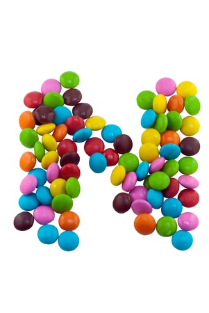 Colorful candies lay in letter N in front of white background photo