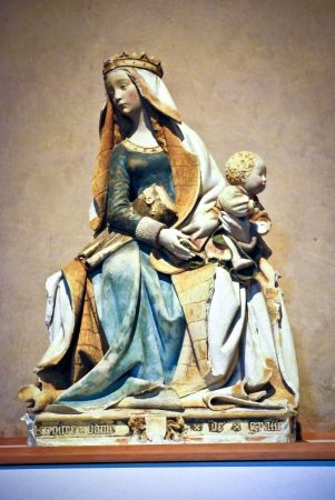 Colored stone statue of the virgin Mary carrying a child