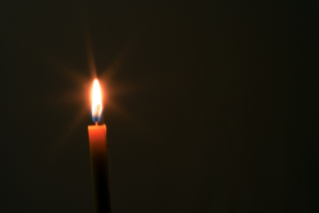 Lonely candle into a darkness. Stock Photo