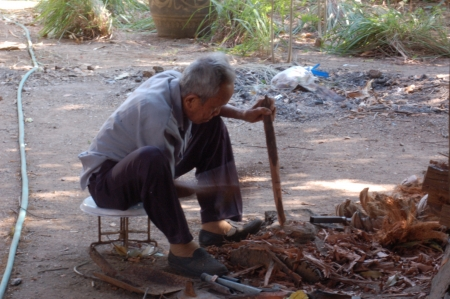 Old carpenter man chop wood to make a hoe handle