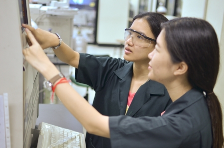 Female researcher teaching student about an apparatus in a laboratory. Editorial