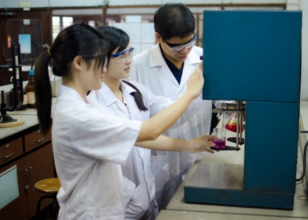 Female medical or scientific researchers or doctors using an apparatus in a laboratory.