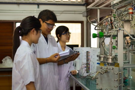 Male medical or scientific researcher teaching female researchers about an apparatus in a laboratory.