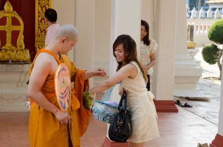 ordination: The lovely lady gives money to a new monks in Buddhist ordination ceremony, Lopburi, Thailand Editorial