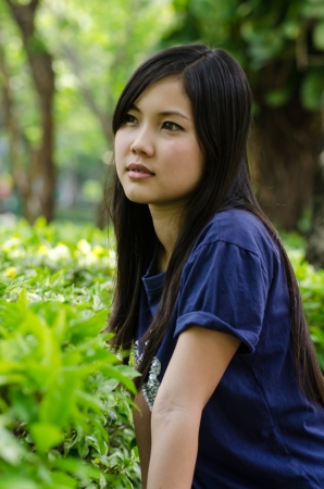 An Asian girl who is waiting in a garden photo