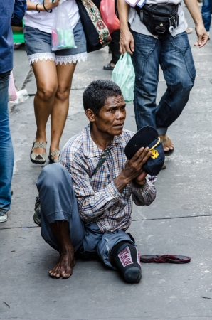 crippled: The man sits by the roadside for passing tourists to make money. Editorial