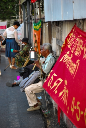 Thai blind man sits by the roadside and plays music for passing tourists and Thai people to make money.
