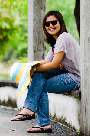 Portrait of a beautiful Asian woman smiling, waring sunglasses,  in garden
