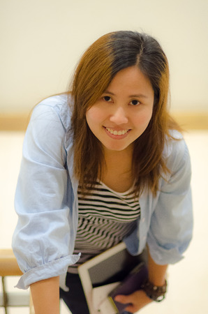 Young Asian woman smiling, holding taplet PC Stock Photo