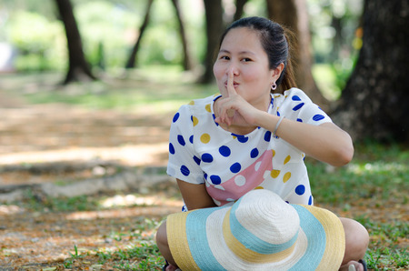 Asian young woman saying hush be quiet, colorful ombrero hat