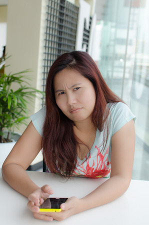 sullen: Angry Thai woman with her yellow phone