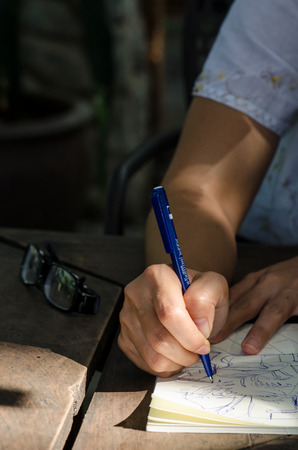 Close-up of a young girl writing into her diary, in the park photo