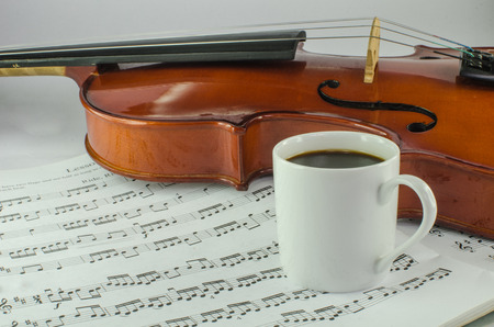 Closeup of violin and cup of coffee on music sheet