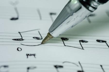 歌: ボールペンで音楽のメモの執筆手のクローズ アップ写真 写真素材
