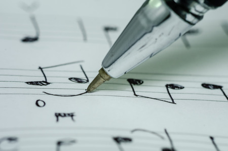 Closeup photo of hand writing music note with ballpoint pen photo