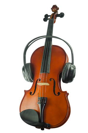 Artistic conceptual close-up of a pair of black headphones on a brown classical wooden violin