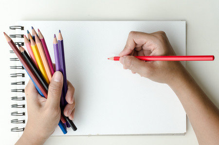 commencing: Man holding a fistful of colored pencils in one hand while commencing sketching in a sketch book to show off his creativity and artistic skills with the other, view from above