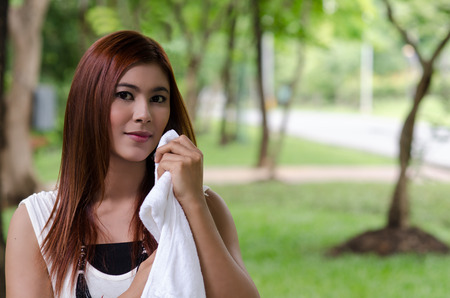 take a breather: Pretty young woman wiping the sweat by a white towel Stock Photo