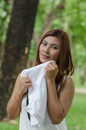 take a breather: Pretty young woman wiping the sweat by a white towel in the park