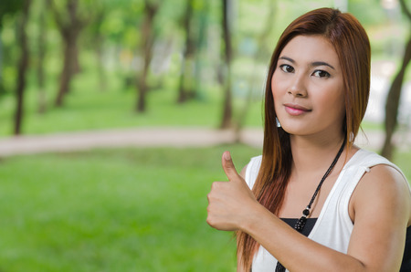 Attractive young Asian woman giving a thumbs up gesture of approval and success as she stands outdoors in a park