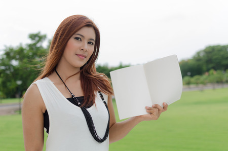 auburn hair: Attractive trendy young Asian woman with long auburn hair holding an open book in her hand as she stands in open countryside smiling at the camera