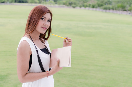 Beautiful young Asian woman relaxing in the countryside carrying a book clutched to her chest as she prepares to spend a peaceful day reading outdoors