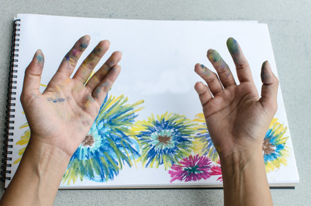 Hand with stained pastel in front of the colorful flower painting Stock Photo