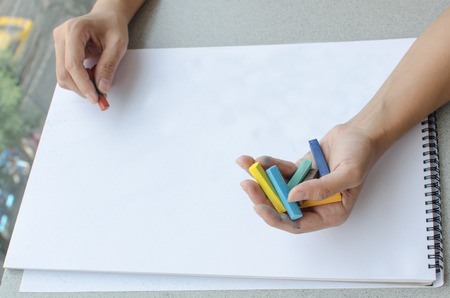 commencing: Man holding a fistful of colored pastel in one hand while commencing sketching in a sketch book Stock Photo