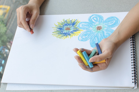 Man holding a fistful of colored pastel in one hand while commencing sketching in a sketch book Stock Photo