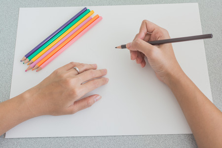 High angle view of the hands of a person sketching with colored pencils on a large blank white sheet of paper with a set of pencil crayons on top and one in his hand