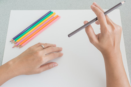 one sheet: High angle view of the hands of a person sketching with colored pencils on a large blank white sheet of paper with a set of pencil crayons on top and one in his hand