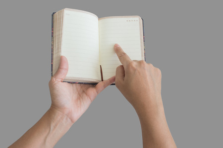 Man holding up a small blank diary opened to a clean white double page spread with copyspace for your text isolated over a grey background. closeup view in raised position as though reading Stock Photo