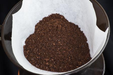 papel filtro: Vista de �ngulo alto de una porci�n de granos de caf� reci�n molido en un papel de filtro listo para hacer de filtro o caf� expreso Foto de archivo
