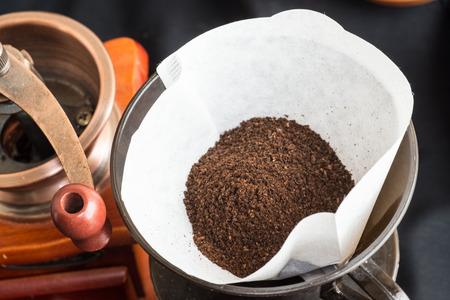 papel filtro: Vista desde arriba de los granos de caf� reci�n molido en un papel de filtro limpio con un molino o triturador junto conceptual de la preparaci�n de una taza de caf�