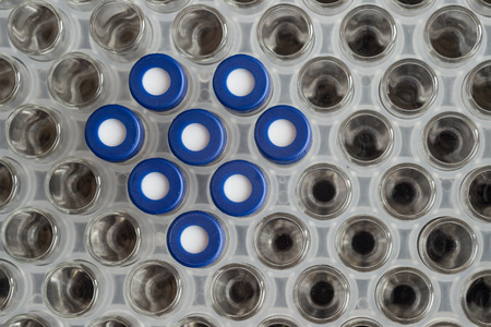 spectrometry: Glass test tubes or containers in a metal rack in an industrial or medical laboratory, view from above with heart shape