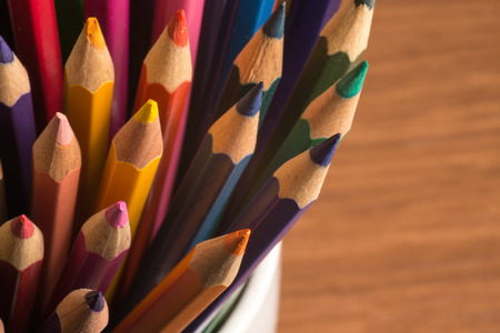 color in: Lápices de colores en blanco taza de café sobre fondo de madera