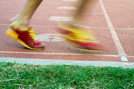 locomotion: Side low angle view of unidentifiable runners leaving a racing track starting line in fast motion