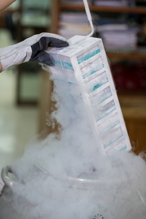 retrieving: Close up of gloved hand retrieving boxes from cryogenic freezer device in laboratory
