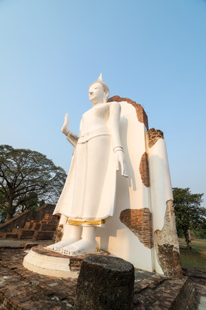 venerate: White Buddha statue in ruins temple facing morning sunlight and clear blue sky Stock Photo