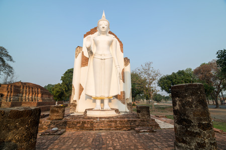White Buddha statue in ruins temple facing morning sunlight and clear blue sky Stock Photo
