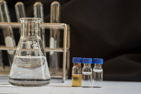 Blue cap vials and out of focus laboratory glassware containing chemicals in science research