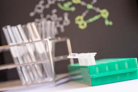 Plastic vials places in green rack in front of chemical formula and test tube