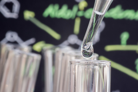 spectrometry: Liquid drop into test tube in front of blur chemical formula