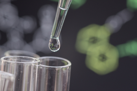 spectrometry: Reflection of chemical formular in water drop on test tube in front of blur chemical formula